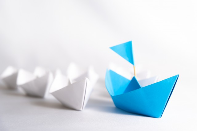Leadership concept. blue paper ship with flag lead among white. One leader ship leads other ships.